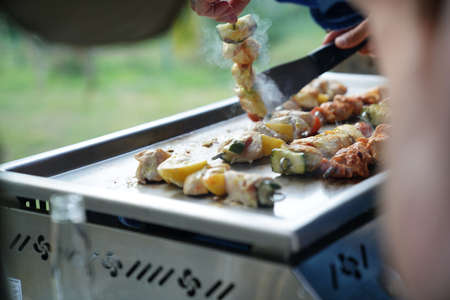 Closeup of chicken skewers cooking on grill
