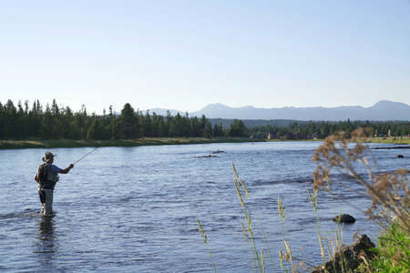 Fisherman flyfishing in river of Idaho state 写真素材
