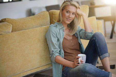 Blond 40-year-old woman relaxing at home 写真素材
