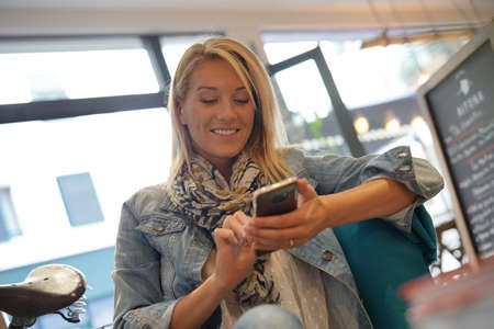 Woman at coffee shop using smartphone