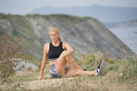 Woman training outside, doing stretching exercises