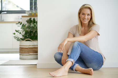 Beautiful blond woman sitting on floor against white wall 写真素材
