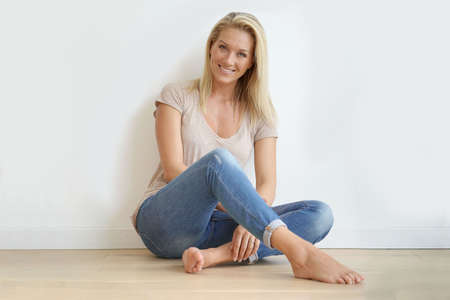 Beautiful blond woman sitting on floor against white wall Reklamní fotografie