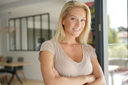 40-year-old blond woman standing inside house