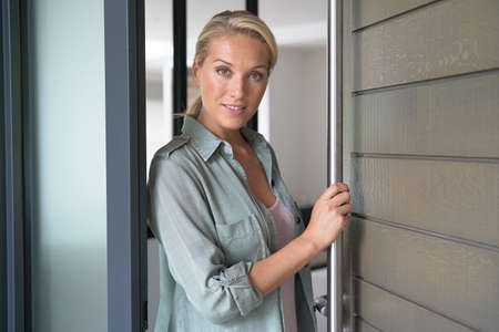 Blond woman welcoming people at entrance front door Reklamní fotografie