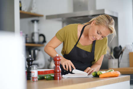 40-year-old woman cooking in home kitchen Reklamní fotografie