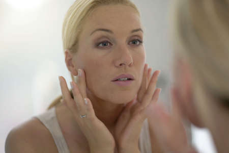 40-year-old woman looking at her face in mirror