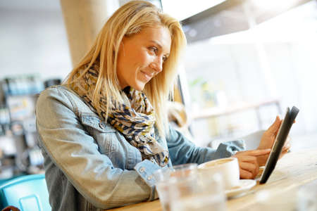 Woman at coffee shop websurfing on digital tablet