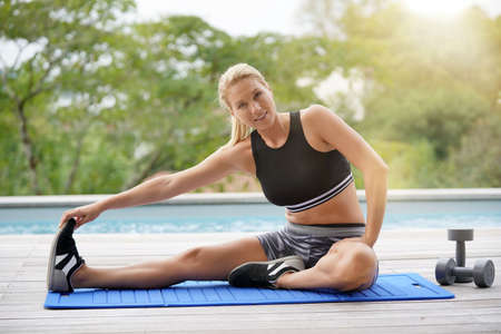 Woman doing fitness exercises outside by the pool