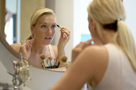 40-year-old woman putting makeup on in front of mirror