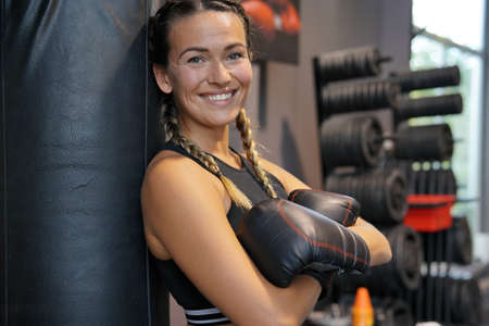 Woman wearing boxing gloves leaning on a punching bag Standard-Bild