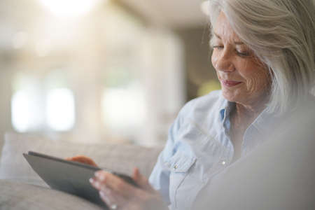 Senior woman at home with tablet