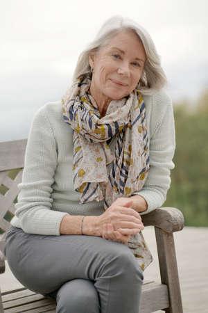Beautiful senior woman sitting outdoors and smiling 版權商用圖片
