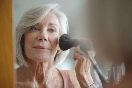 Beautiful elderly woman applying make up