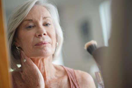 Attraktive ältere Frau, die ihre Haut im Spiegel betrachtet