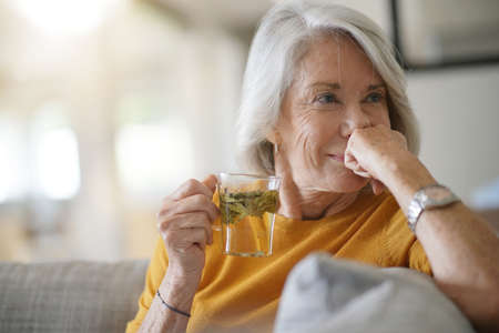 Beautiful senior woman at home with cup of loose leaf tea