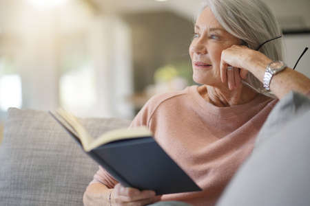 Senior woman reading on couch at home 版權商用圖片