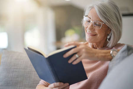 Senior woman reading on couch at home Stock Photo