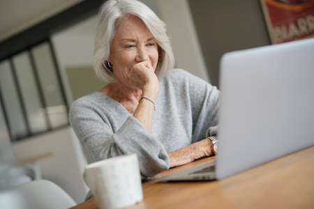 Elderly woman at home with computer Standard-Bild