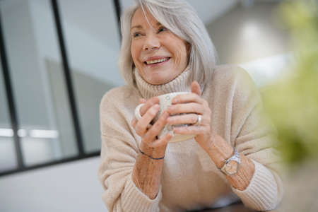 Senior woman at home with hot drink