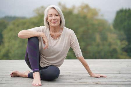 Schöne ältere Frau, die draußen in Sportkleidung sitzt