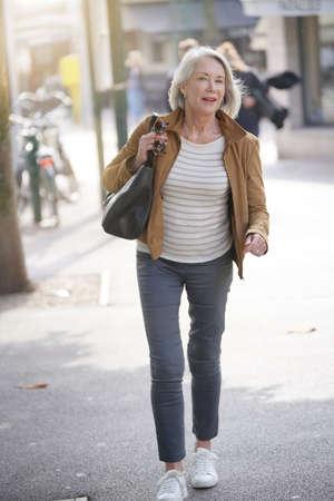 Attractive senior woman walking through town