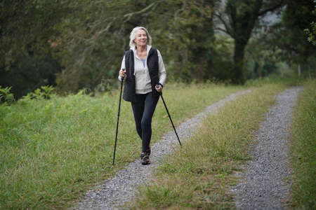 Senior woman nordic walking in the countryside
