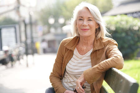 Lovely senior woman sitting on bench outdoors
