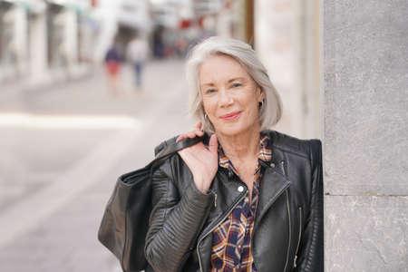 Retrato, de, moderno, mujer mayor, en, ciudad, llevando, chaqueta de cuero
