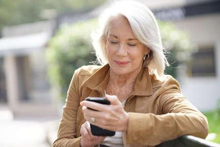 Beautiful senior woman texting outdoors Stock Photo