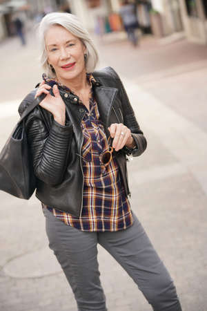 Modern senior woman in town wearing leather jacket