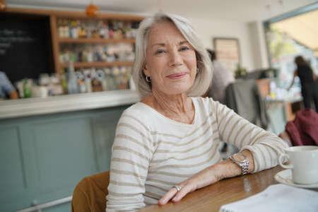 Portrait of attractive senior woman in restaurant Stock Photo