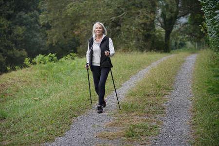 Ältere Frau Nordic Walking auf dem Lande