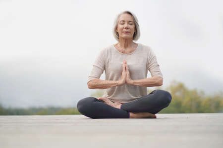 Serene senior woman meditating outdoors Stock fotó - 110688632