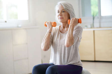 Attractive elderly woman exercising at home with swiss ball