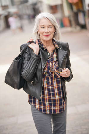 Modern senior woman in town wearing leather jacket