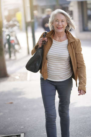 Attractive senior woman walking through town