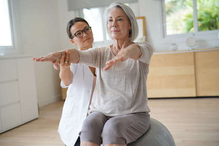 Senior woman exercising with her physiotherapist and swiss ball Archivio Fotografico