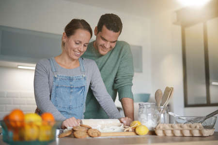 Happy young couple baking together at home Banco de Imagens