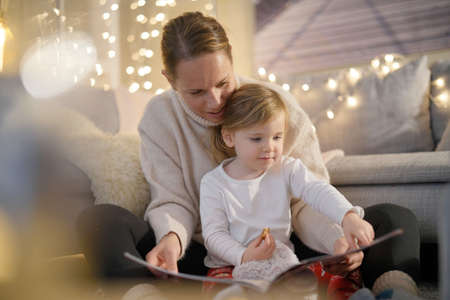 Cosy mother and daughter reading a story at home Imagens