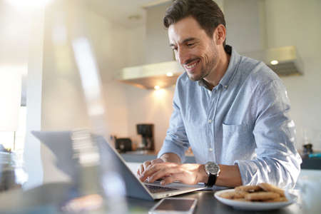 Handsome man with computer in modern kitchen