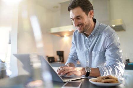 Handsome man with computer in modern kitchen Foto de archivo