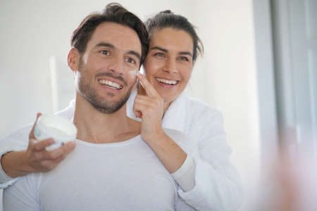 Stunning brunette applying face cream on her handsome partner