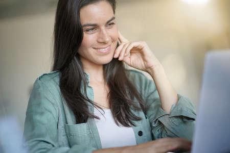 Portrait of stunning brunette smiling at her laptop Archivio Fotografico