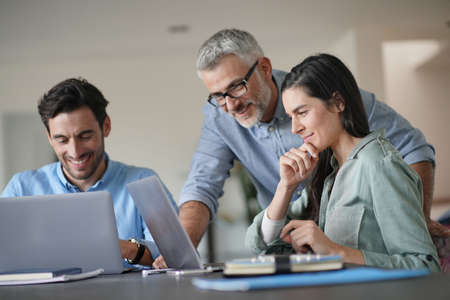 Jóvenes colegas con jefe mayor trabajando con computadoras Foto de archivo
