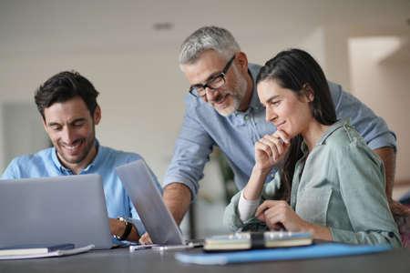 Młodzi koledzy ze starszym szefem pracują z komputerami Zdjęcie Seryjne