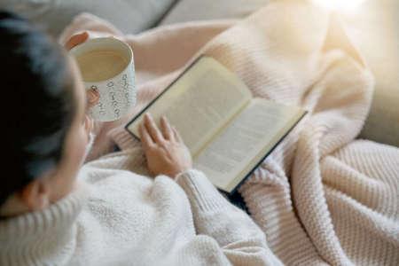 Acogedora morena en casa en el sofá con bebida caliente y lectura