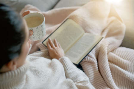 Cosy brunette at home on couch with hot drink and reading Stok Fotoğraf