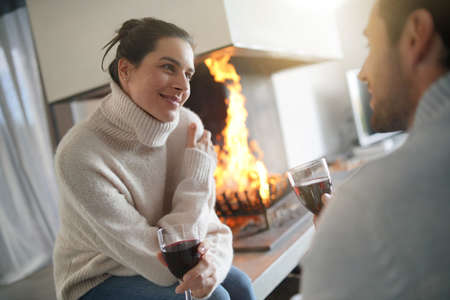 Couple relaxing by the fire enjoying glass of red wine Banco de Imagens - 113758384