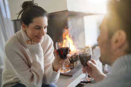 Couple relaxing by the fire enjoying glass of red wine Stock Photo